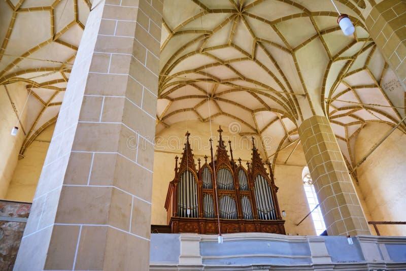 Inre med organet, detvälvde taket och pelare i det Biertan stärkte bullret Biertan för kyrkaBiserica fortificata arkivbilder