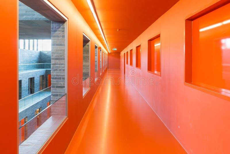 Inre modern byggnad med flera den målade golv och apelsinen passerar arkivfoto