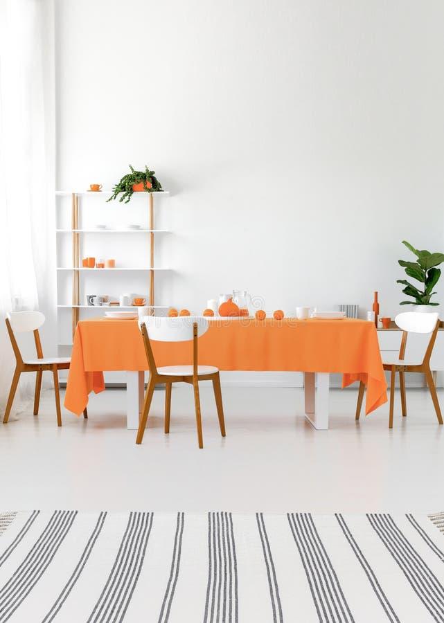 inre modernt Lång matsaltabell med stolar Vitt väggar och golv, orange detaljer Verkligt fotobegrepp royaltyfri bild