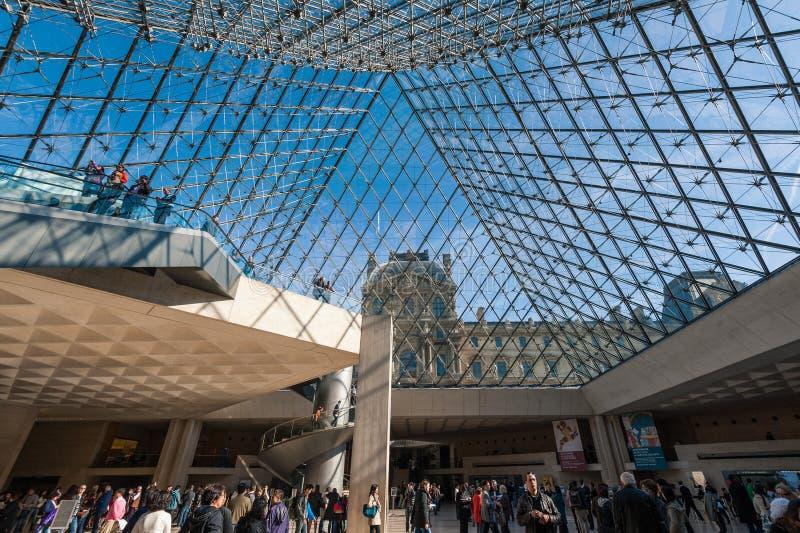Inre och besökare på den huvudsakliga ingången av Louvremuseet royaltyfri foto