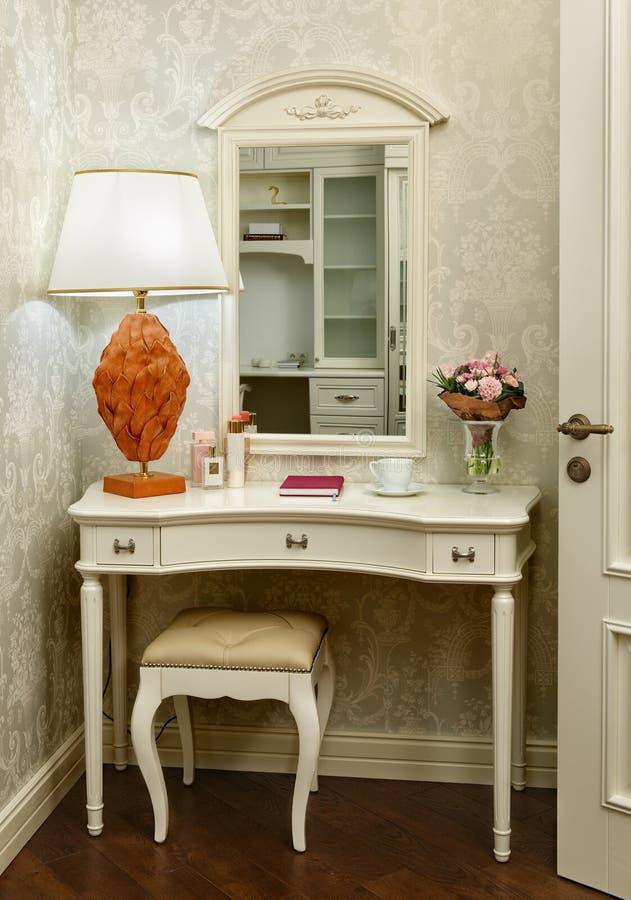 Inre rum med dressingtabellen, stolen och tabelllampan arkivfoto