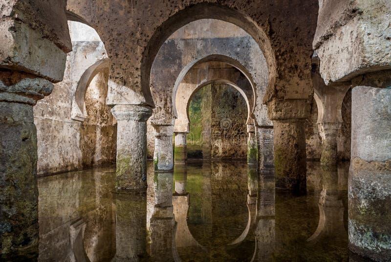 Inre sikt av den arabiska cisternen Caceres Spanien, reflexioner av bågarna i vattnet royaltyfri fotografi