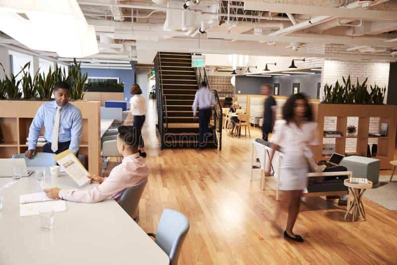 Inre sikt av det moderna öppna plankontoret med suddiga affärsmän och affärskvinnor fotografering för bildbyråer