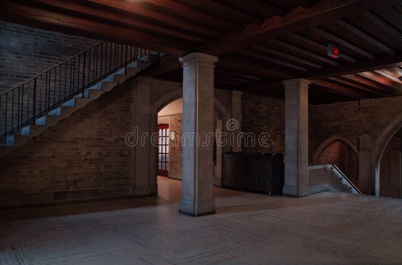 Inre sikt av en gammal byggnad med kolonner och trappan med n?gra ljusa str?lar i m?rkt omge royaltyfria bilder