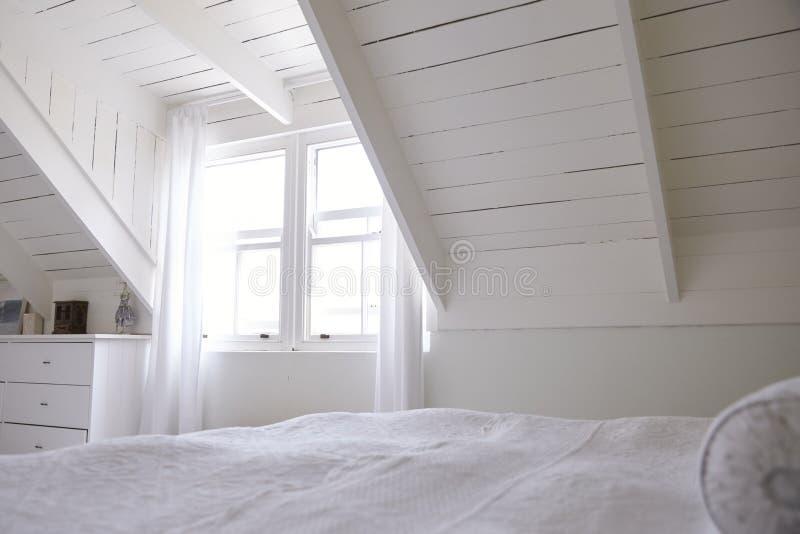 Inre sikt av härligt ljus och Airy White Bedroom royaltyfria bilder