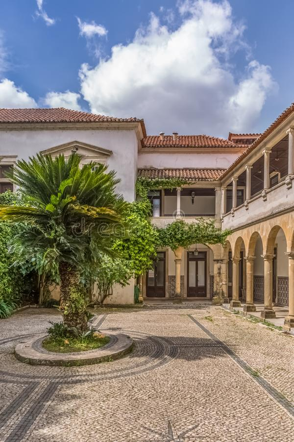 Inre sikt av universitetet av Coimbra, byggnad för lagavdelning, Melos slott, med trädgården och den vernacular kloster royaltyfri foto