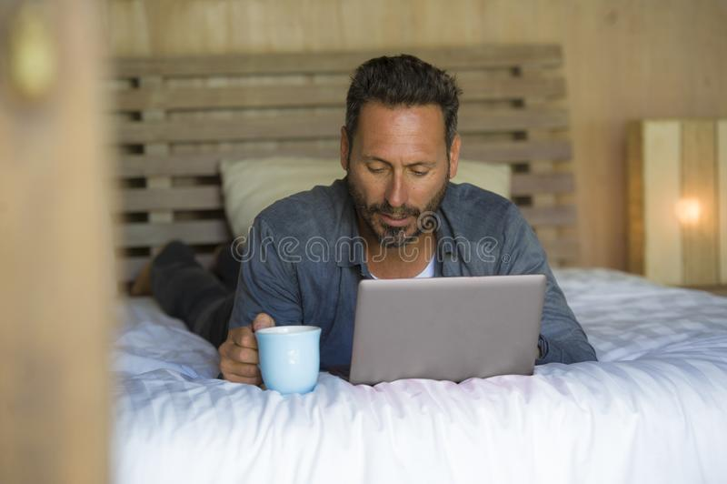 Inre stående av ungt attraktivt och lyckligt arbeta för man som hemma är avkopplat på säng med att le för bärbar datordator som ä royaltyfria foton