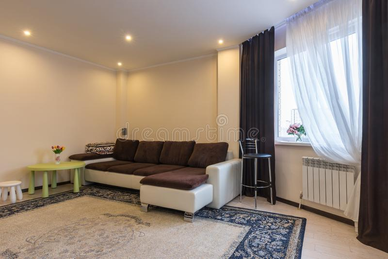 Inre stort soffa för vardagsrum och fönster med mörka gardiner arkivfoton