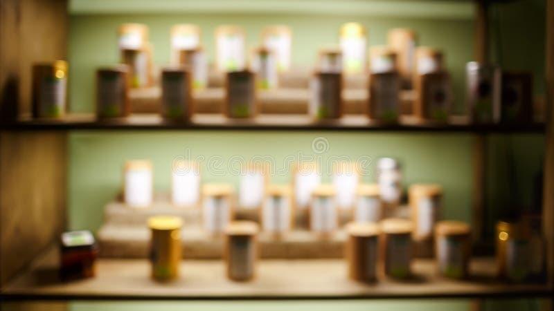 Inre suddig abstrakt bakgrund för tecoffee shop, hyllor med prövkopior, tillbaka ljus sortiment arkivfoton