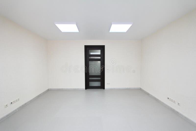 Inre tomt kontorsljusrum med den vita tapeten som är omöblerad i en nybygge fotografering för bildbyråer