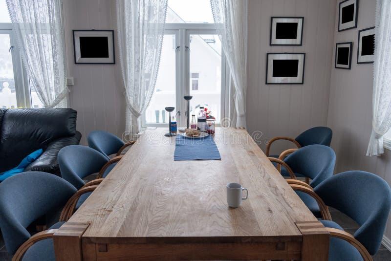 Inre trääta middag tabell med stolar och den tomma bildramen royaltyfri fotografi