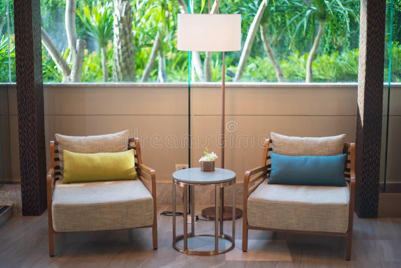 Inre vardagsrum för brun träför sidotabell för stol två stil lyxig royaltyfria foton