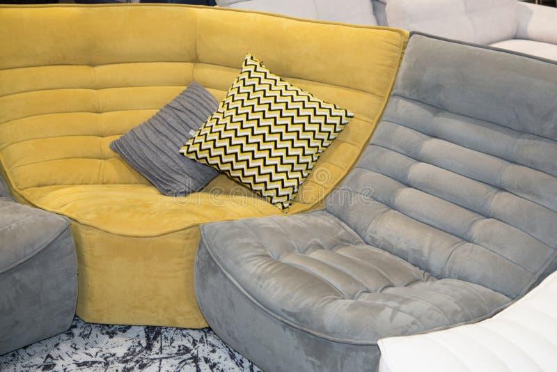 Inre vardagsrum med den stora vinkelsoffan som en grå färg för gul gräsplan uttrycker royaltyfri fotografi