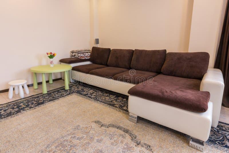 Inre vardagsrum, stor soffatabell och stol arkivbilder