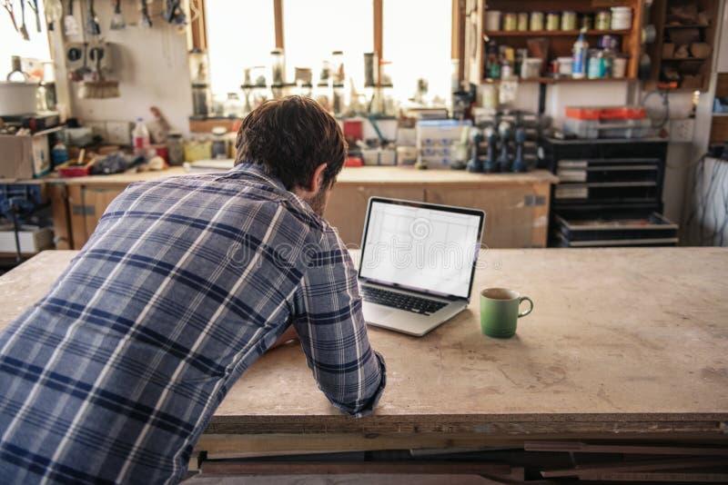 Inredningssnickare som direktanslutet arbetar med en bärbar dator i hans seminarium fotografering för bildbyråer