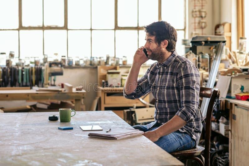 Inredningssnickare som sitter på en arbetsbänk som talar på hans mobiltelefon royaltyfri foto