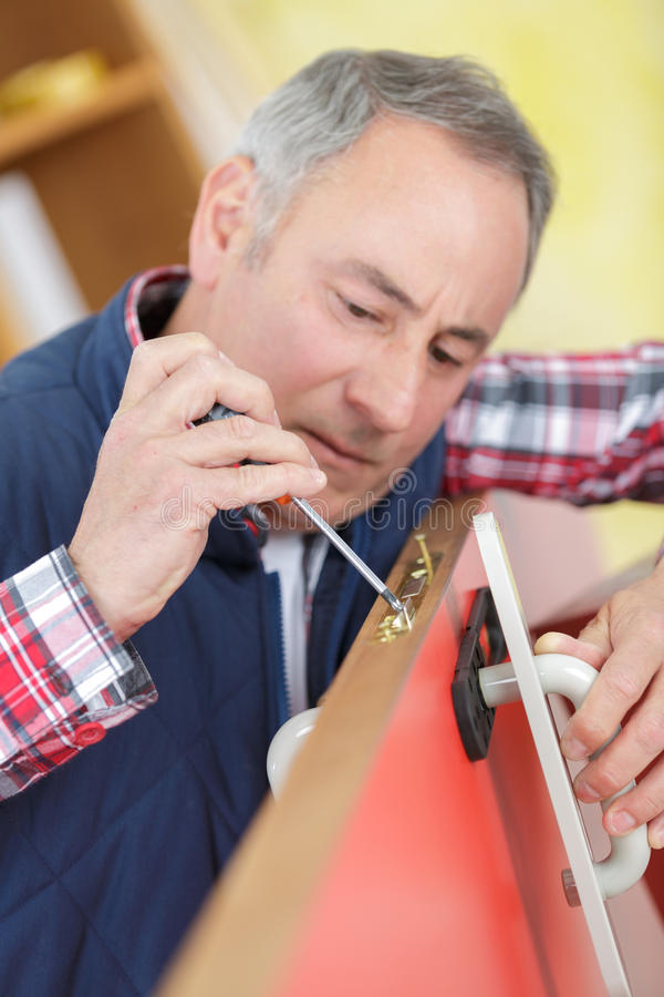 Inredningssnickaren installerar dörren genom att använda skruvmejseln arkivbild