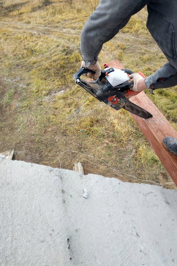 inredningssnickaren med en chainsaw gör drack på en trästrålkonstruktion av hus royaltyfria foton