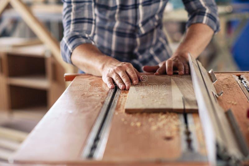 Inredningssnickaren som gör precisionsnitt med en tabell, såg arkivfoto