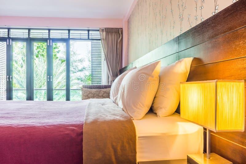 Inregarnering av det moderna sovrummet med breda exponeringsglasbalkongdörrar royaltyfria bilder