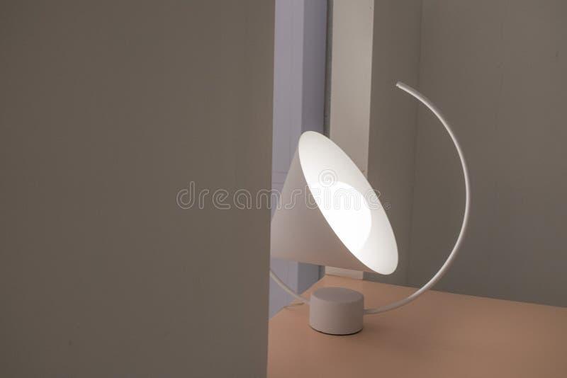 Inregarnering med den ojämna lampan på tabellen och vit vägg arkivbild
