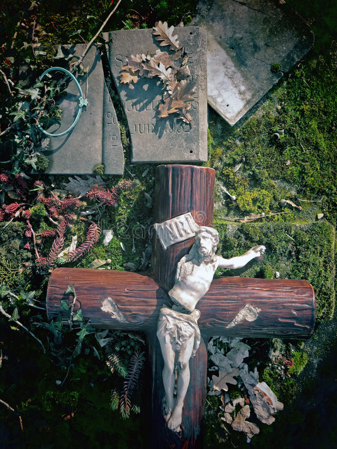 INRI #2. An old crucifix and broken and abandoned headstone. Photo Effect saturated with light and bright colors stock photo