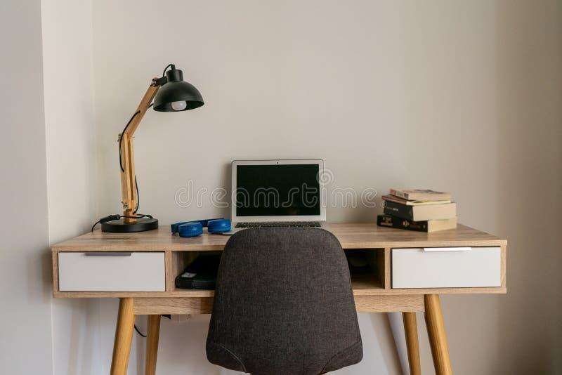 Inrikesdepartementetskrivbord med bärbara datorn och böcker arkivbild