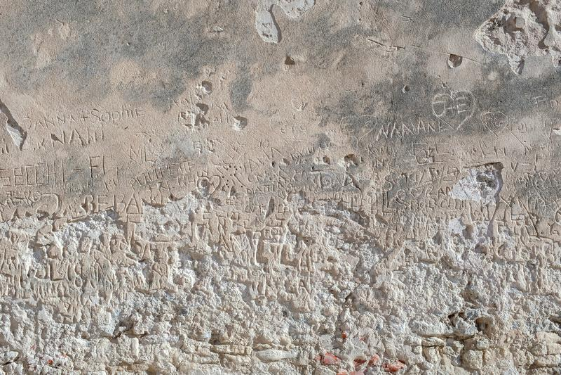 Inristade handstilar på stenväggen av turister som visar deras passage-meddelande, namn fotografering för bildbyråer