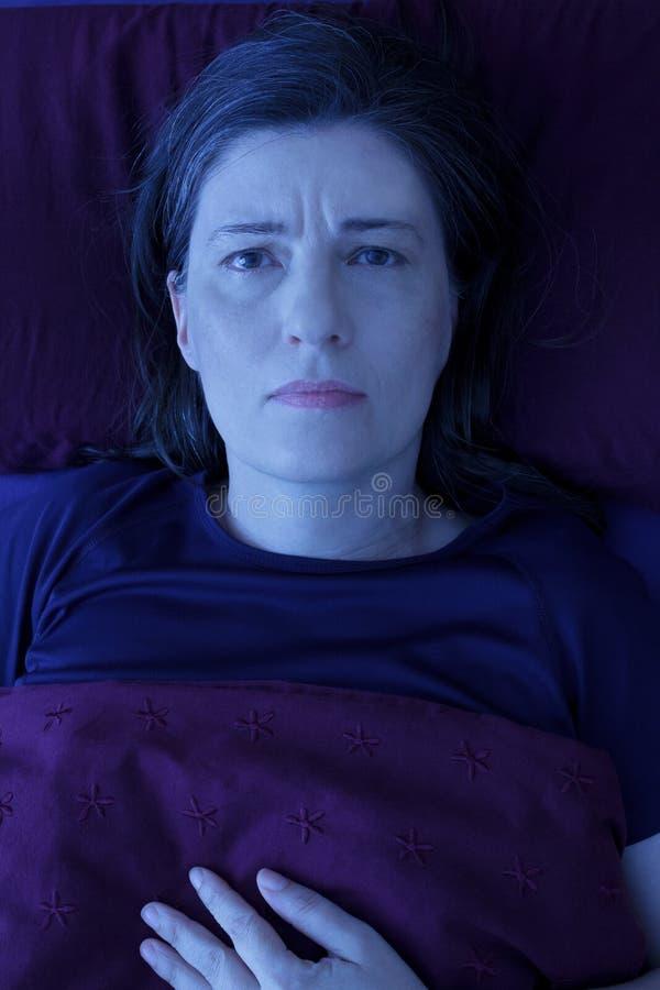 Insônia acordada da noite da cama da mulher foto de stock
