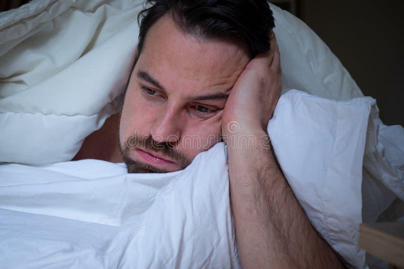 Insônia ansiosa do sofrimento do homem furada na cama fotografia de stock