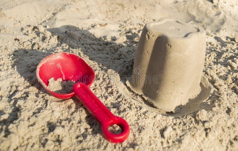 Insabbi i giocattoli, un secchio rosso e un mestolo sulla sabbia, immagini stock