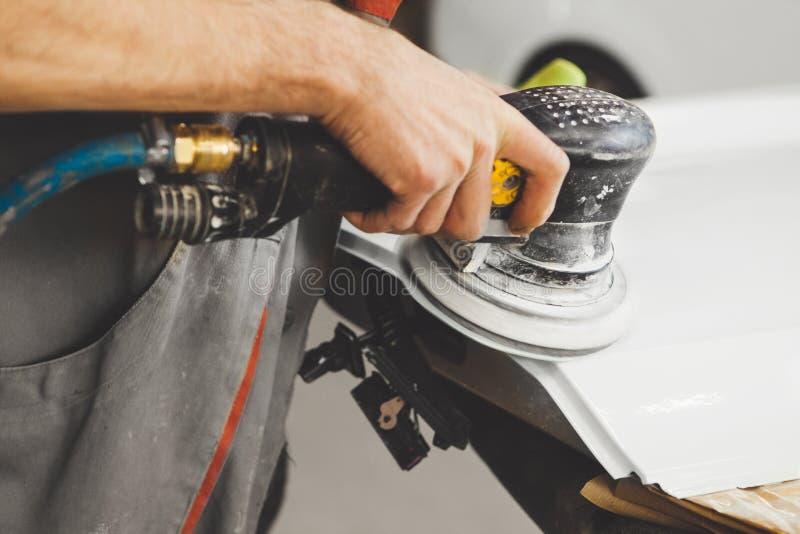 Insabbiamento degli elementi irregolari dell'automobile dopo la verniciatura e la verniciatura Riparazione del veicolo in distrib fotografie stock