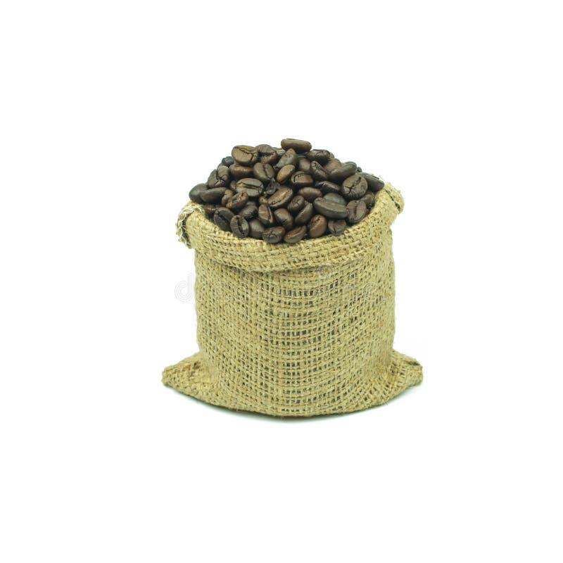 Insacchi con i chicchi di caffè isolati sui precedenti bianchi fotografia stock
