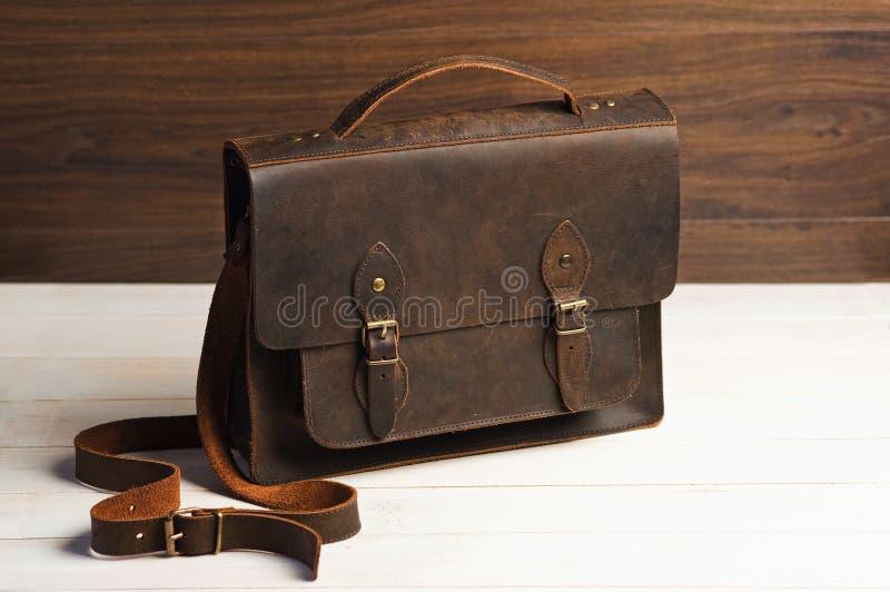 Insacchi la cartella per gli uomini dell'uomo d'affari, borsa marrone di cuoio su un fondo di legno Modo del ` s degli uomini, ac immagine stock libera da diritti