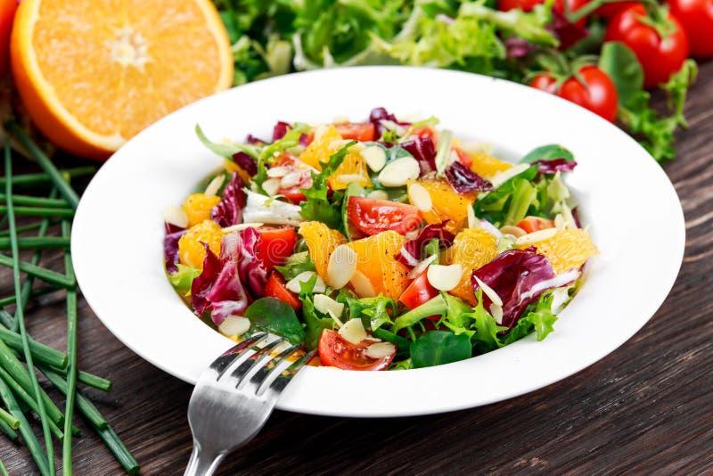 Insalata arancio fresca delle verdure con la mandorla sfaldata Sulla tabella di legno immagini stock