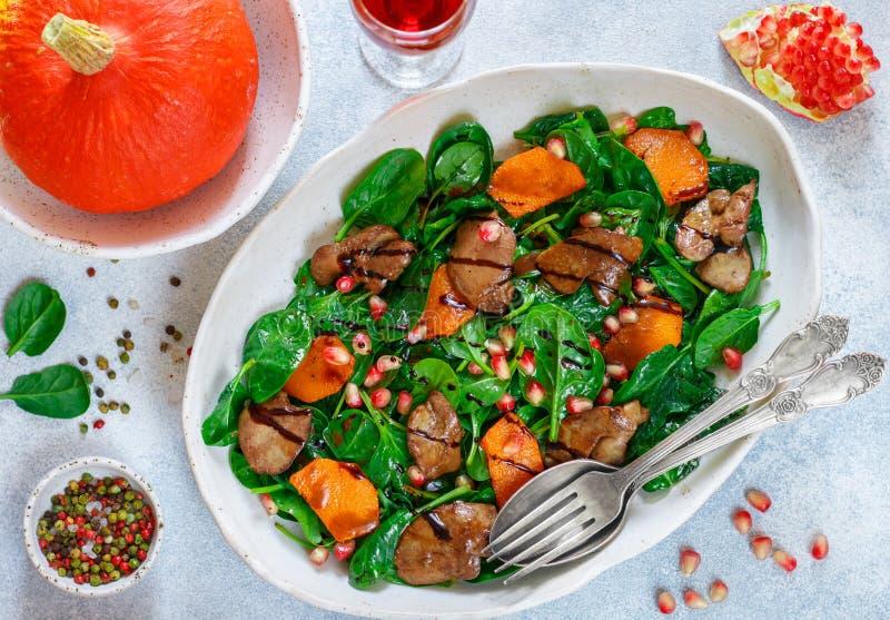 Insalata calda degli spinaci con il fegato di pollo, la zucca al forno ed il melograno fotografie stock