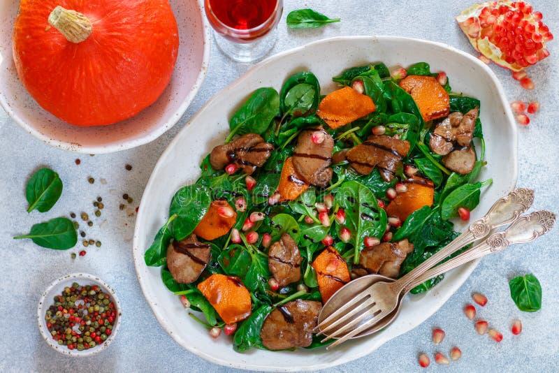 Insalata calda degli spinaci con il fegato di pollo, la zucca al forno ed il melograno immagine stock