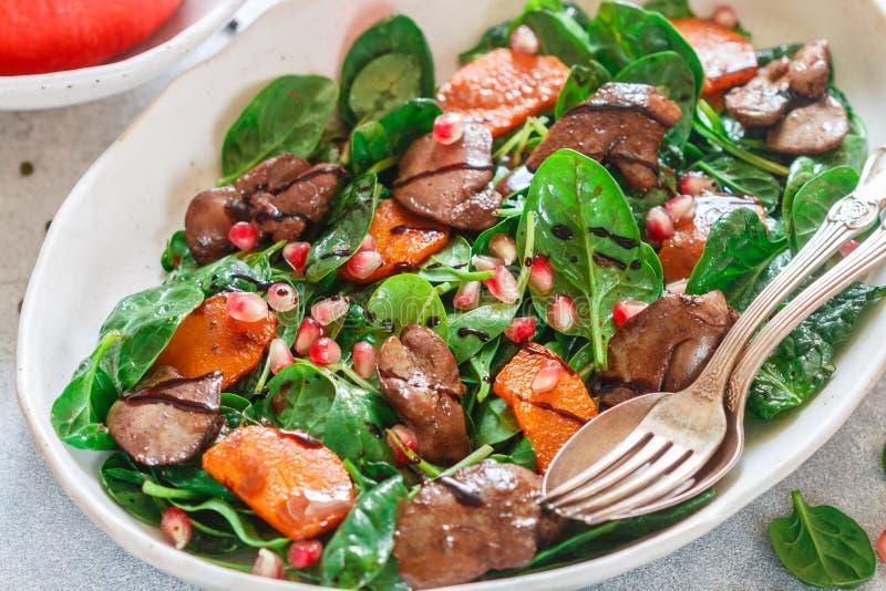Insalata calda degli spinaci con il fegato di pollo, la zucca al forno ed il melograno immagini stock