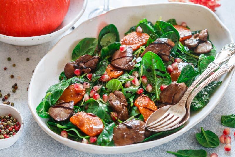 Insalata calda degli spinaci con il fegato di pollo, la zucca al forno ed il melograno immagini stock libere da diritti