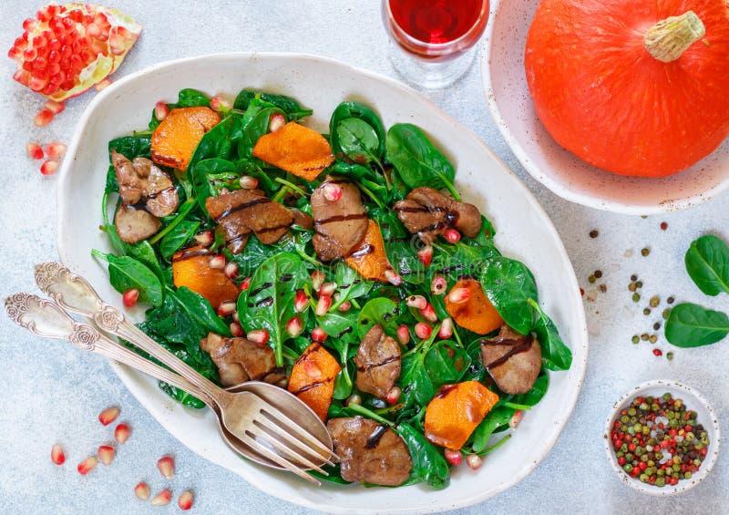 Insalata calda degli spinaci con il fegato di pollo, la zucca al forno ed il melograno fotografie stock libere da diritti