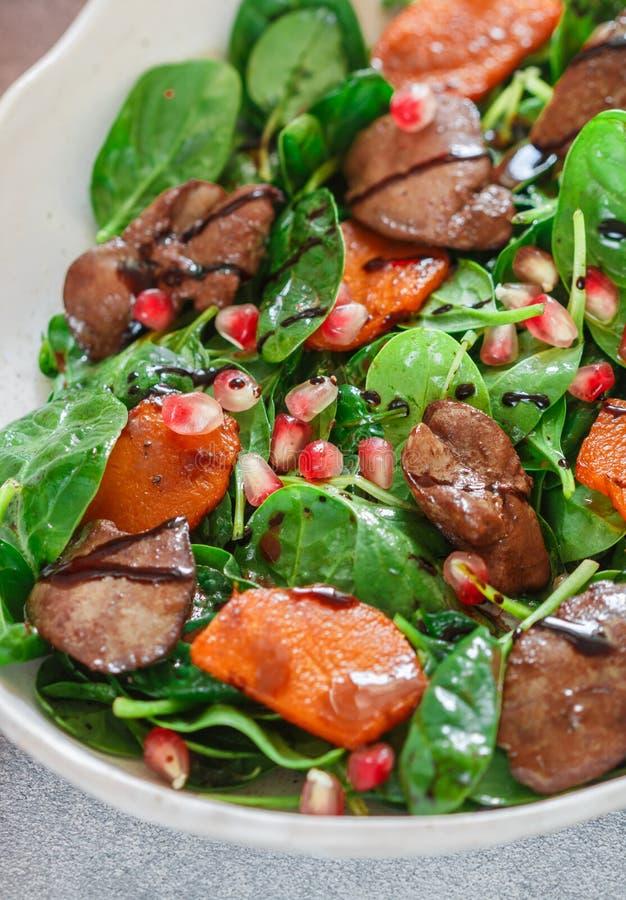 Insalata calda degli spinaci con il fegato di pollo, la zucca al forno ed il melograno fotografia stock