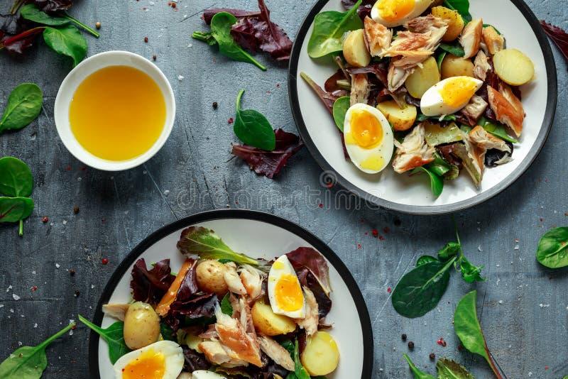 Insalata calda dello sgombro affumicato con la patata novella, uova, preparato verde della lattuga in un piatto immagine stock libera da diritti