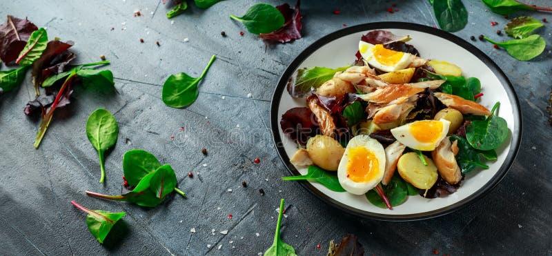 Insalata calda dello sgombro affumicato con la patata novella, uova, preparato verde della lattuga in un piatto immagini stock libere da diritti