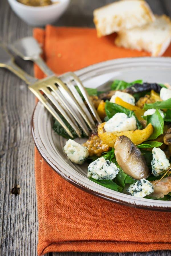 Insalata calda di autunno con le patate, i funghi, il bacon, gli spinaci, la salsa di senape ed il formaggio sul tovagliolo aranc fotografia stock libera da diritti