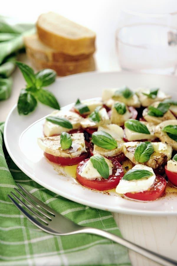 Insalata caprese fresca con i pomodori + la mozzarella e i bas deliziosi fotografie stock libere da diritti