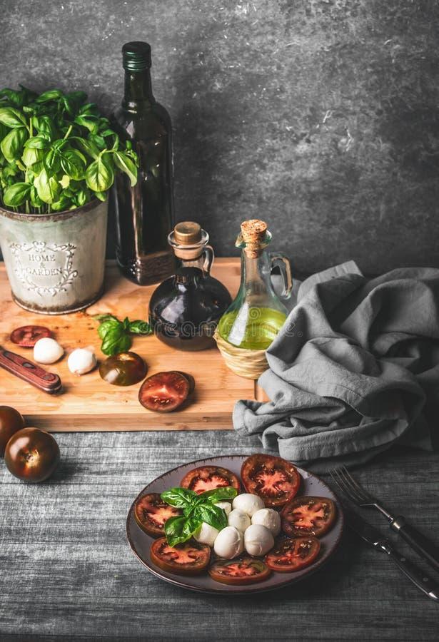 Insalata caprese italiana deliziosa servita sulla tavola rustica con le piante aromatiche del basilico e la bottiglia conservate  fotografia stock libera da diritti