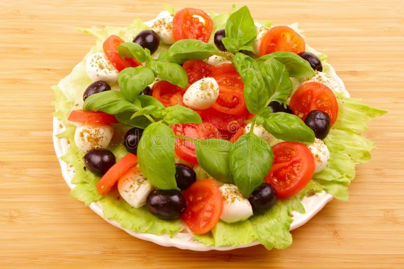 Insalata con basilico, la mozzarella, le olive ed il pomodoro fotografie stock libere da diritti