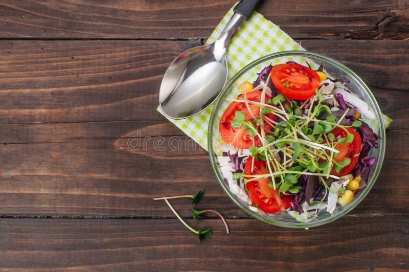 Insalata con cavolo rosso, i germogli del ravanello, il mais ed i pomodori su fondo di legno con lo spazio della copia immagini stock libere da diritti