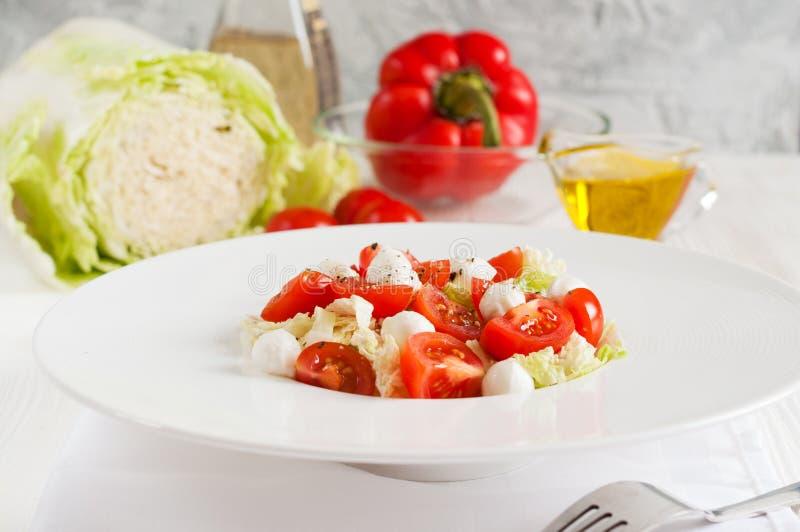 Insalata con i pomodori ciliegia, la mozzarella ed i verdi immagini stock libere da diritti