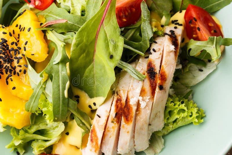 Insalata con il pollo arrostito, mango, lattuga, avocado, pomodori, rucola, sause del formaggio su un piatto bianco su di legno fotografia stock